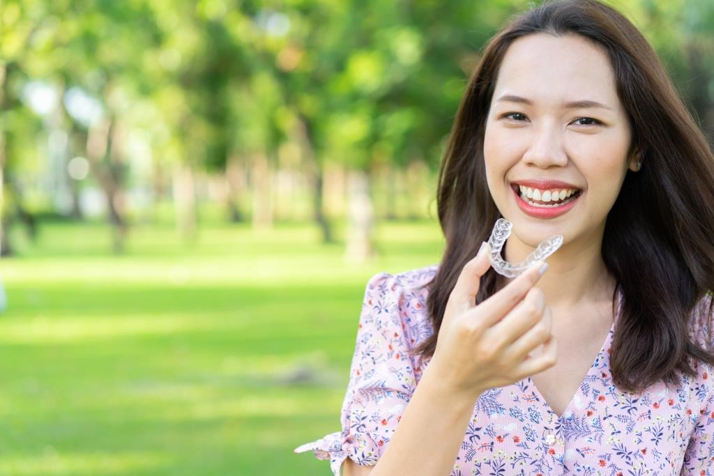 orthodontics consultation Manassas | Woman holding aligners.