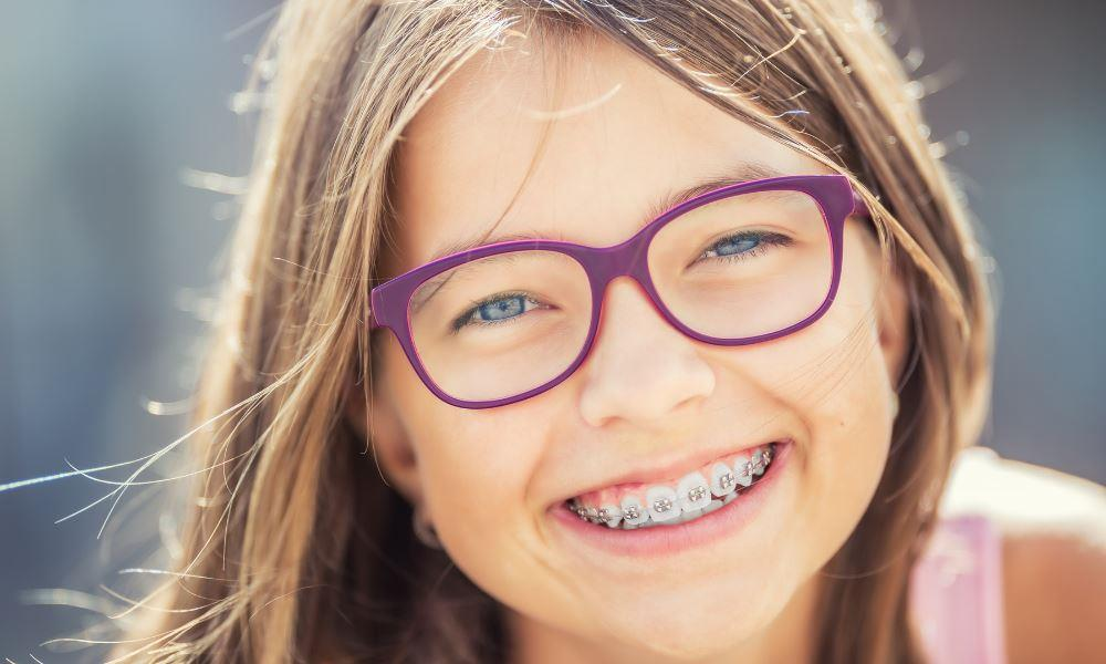 : Family Orthodontic Services Herndon | Young child with braces smiling.